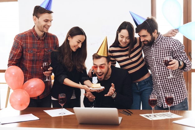 A group of office employees celebrate company birthday
