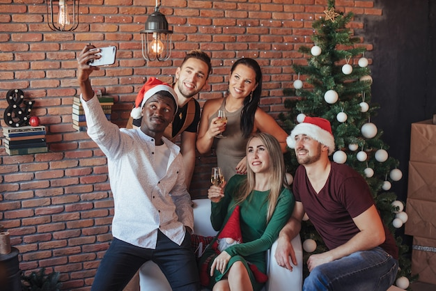 Group of a old friends communicate with each other and make a christmasselfie photo.