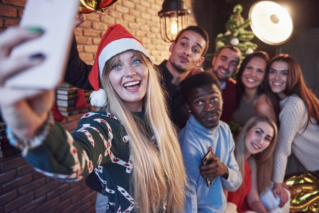 Group of old friends communicate with each other and make a selfie photo. new year is coming. celebrate the new year in a cozy home atmosphere