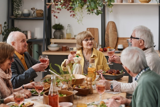 Group of old friends sitting at dining table and drinking wine while celebrating the holiday together at home