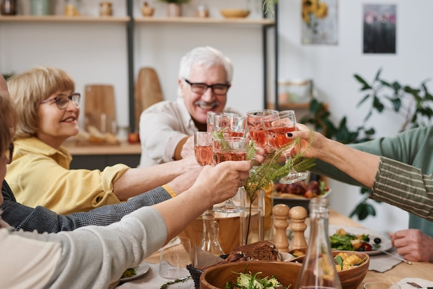 Group of old friends toasting with glasses of red wine while sitting at dining table