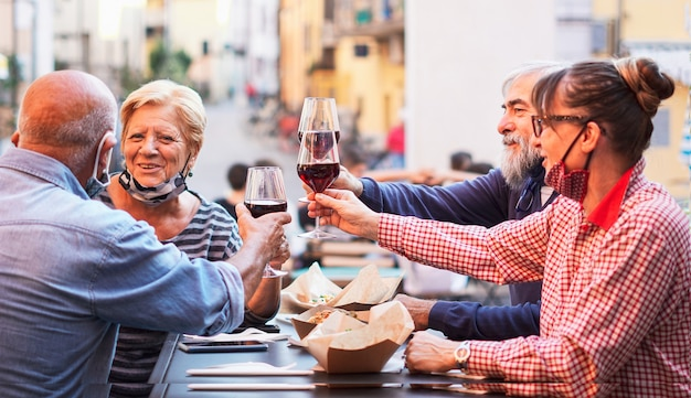 Group of old people eating and drinking outdoors