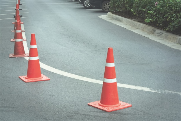 Group of orange traffic cones on curved road