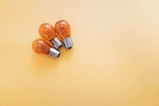 Group of p21 12v car rear brake light bulbs isolated on yellow background.