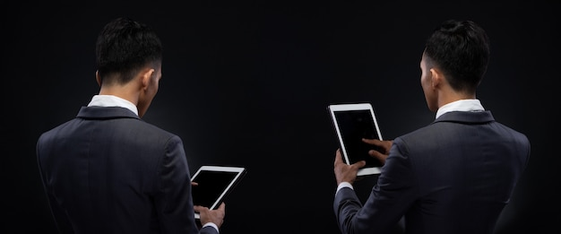 Групповой пакет коллаж портрета азиатского делового мужчины 20-х годов при студийном освещении на темном фоне, мужчина в правильном сером костюме держит цифровой планшет в руке и проверяет социальные сети, читает отчет по электронной почте, iot