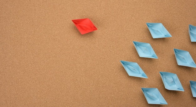 Group of paper boats on a brown background. concept of a strong leader in a team, manipulation of the masses, following new perspectives, collaboration and unification. startup