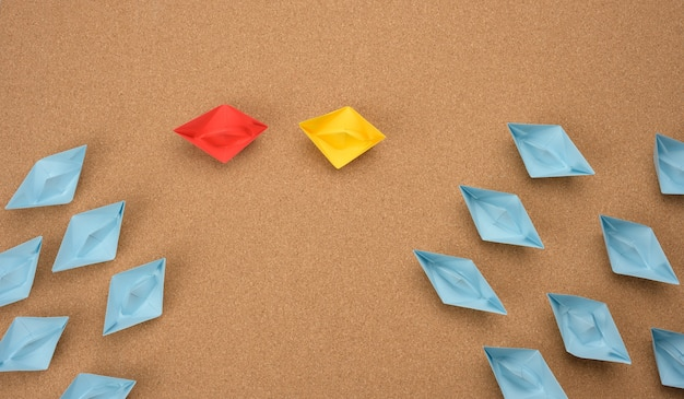 Group of paper boats on a brown background. concept of a strong leader in a team, manipulation of the masses, following new perspectives, collaboration and unification