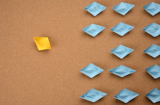 Group of paper boats on a brown surface. concept of a strong leader in a team, manipulation of the masses, following new perspectives, collaboration and unification. startup