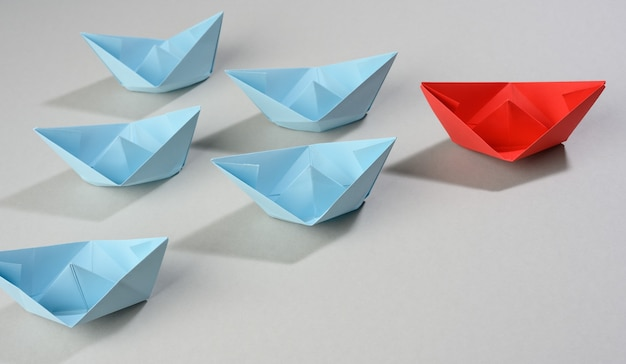 Group of paper boats on a gray background. concept of a strong leader in a team, manipulation of the masses, following new perspectives, collaboration and unification. startup