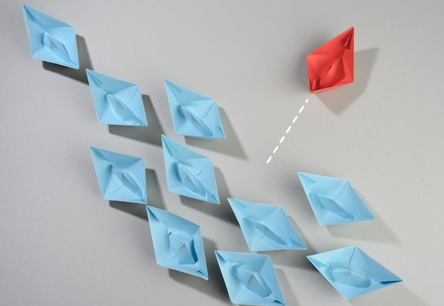Group of paper boats on a gray surface. the concept of thinking outside the box, uniqueness. to act contrary to generally accepted norms