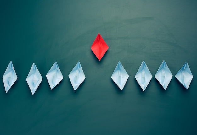 Group of paper boats on a green background. concept of a strong leader in a team, manipulation of the masses, following new perspectives, collaboration and unification. startup