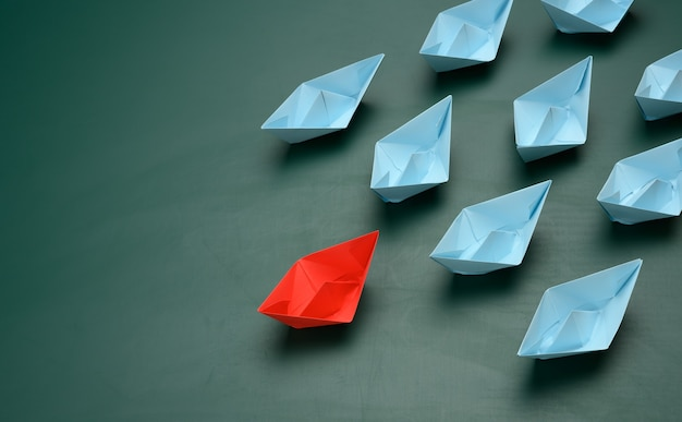 Group of paper boats on a green surface. concept of a strong leader in a team, manipulation of the masses, following new perspectives, collaboration and unification. startup