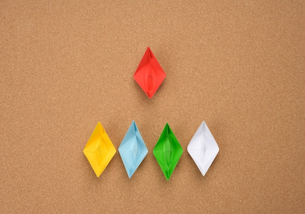 Group of paper boats and one red on abrown surface. the concept of a strong leader, manipulation of the masses, a close-knit team and effective management