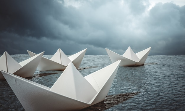 Group of paper boats sailing in open ocean.