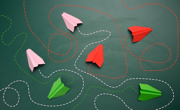 Group of paper planes with long tangled paths on a green background. concept of a strong leader with extraordinary thinking, quick decision-making. finding the optimal and simple solution in business