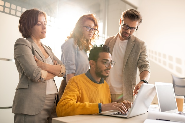 Group of pensive creative advertisers standing at desk and asking web designer to add design elements for presentation in office