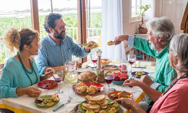 Group of people of all ages eating together at home food - happy adults and seniors togetherness - have lunch indoors