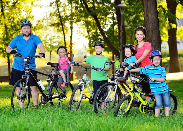 A group of people on bicycles - two adults and four young children in bicycle gear and helmets against the surface of trees, park and green grass