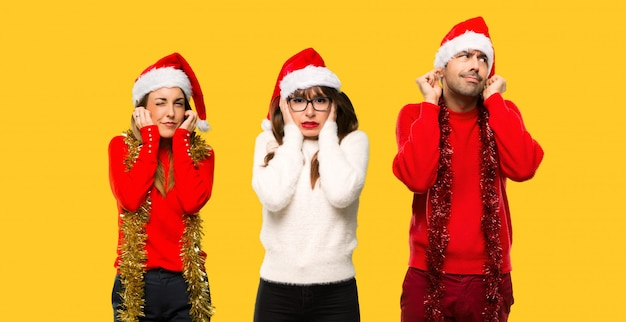 A group of people blonde woman dressed up for christmas holidays covering ears with hands.