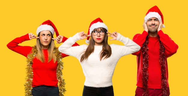 A group of people blonde woman dressed up for christmas holidays covering ears
