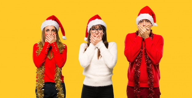 A group of people blonde woman dressed up for christmas holidays covering mouth