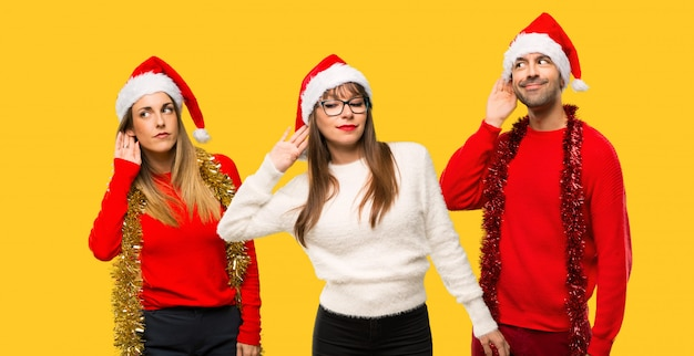 A group of people blonde woman dressed up for christmas holidays listening to something