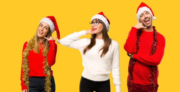 A group of people blonde woman dressed up for christmas holidays making phone gesture