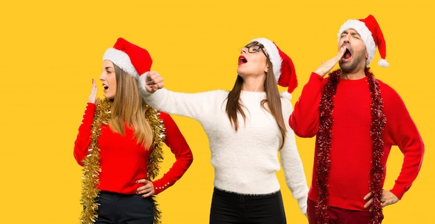A group of people blonde woman dressed up for christmas holidays yawning