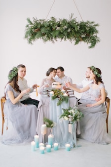 Group of people, bride and groom, bridesmaids and groommen sitting at wedding table with wedding cake, pine decoration and candles in white decorated hall