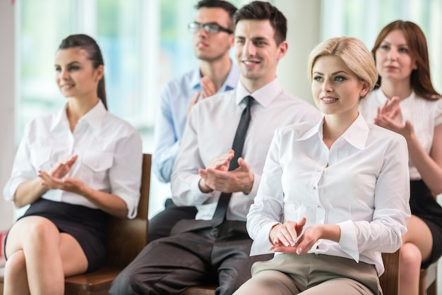 Group of people clapping hands during a meeting.
