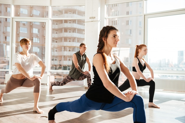 Group of people doing exercises in yoga studio
