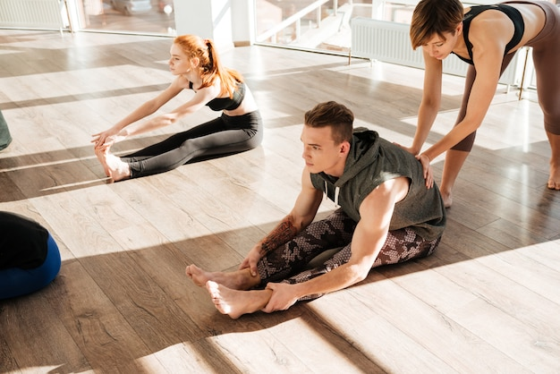 Group of people doing stretching yoga exercises with instructor