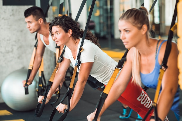 Group of people doing workout with fitness strap in health club