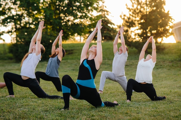 A group of people doing yoga in the park