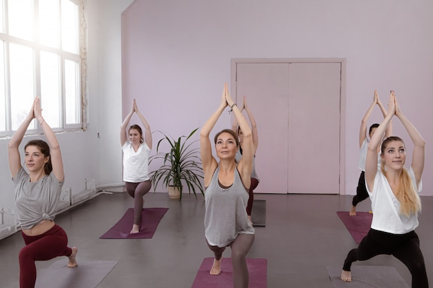 Group of people doing yoga warrior pose at gym