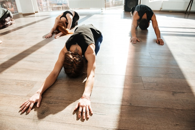 Group of people doing yoga on wooden floor in studio