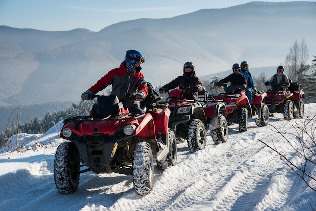 Group of people driving off-road quad bikes on snow at top of the mountain in winter