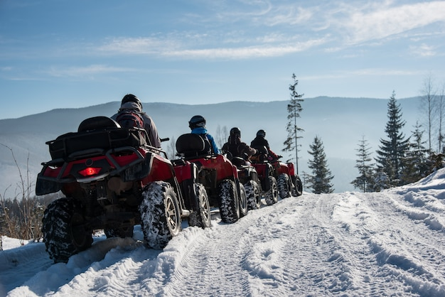 Group of people driving quad bikes on snow at top of the mountain in winter