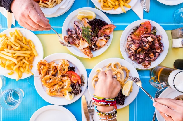 Group of people eating and drinking together - eat fish and healthy food - table with plate with food