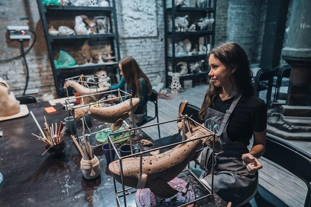 Group of people enjoying favorite job in workshop. people carefully work on ceramic whales