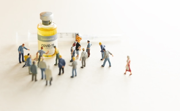 Group of people (figurine) standing against the coronavirus covid-19 vaccine and  syringe for injection .coronavirus vaccine, population immunization campaign concept background.