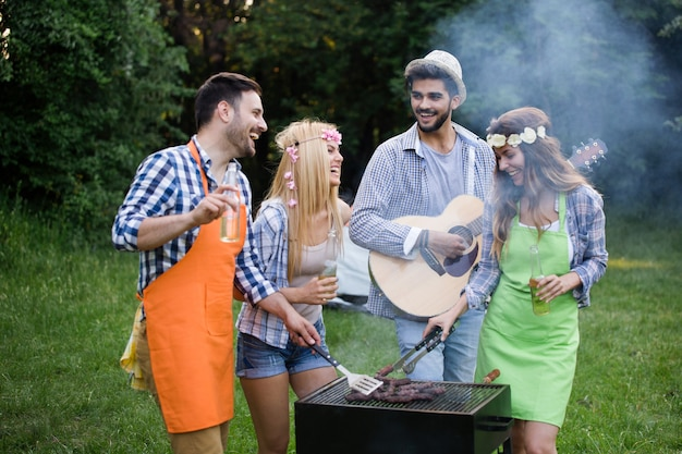 Group of people friends standing around grill, chatting, drinking and eating.