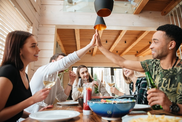 Group of people having dinner and giving high five