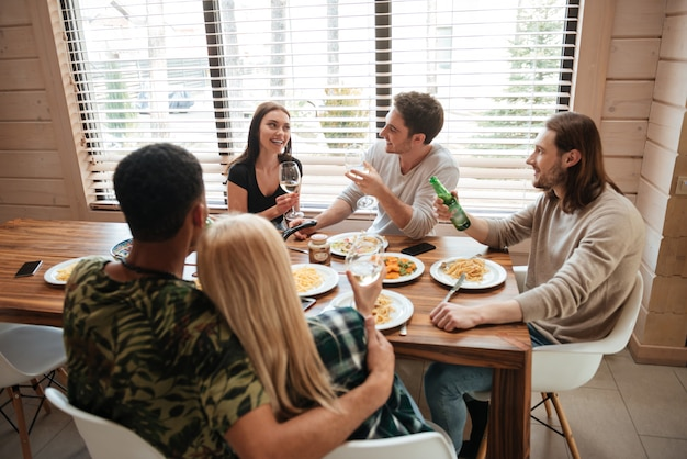 Group of people having dinner and talking on the kitchen