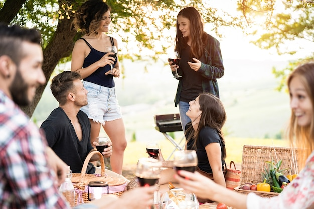 Group of people having fun eating and drinking wine at picnic party outdoors