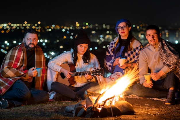 Group of people having fun sitting near bonfire outdoors at night playing guitar, singing songs and talking happily together.