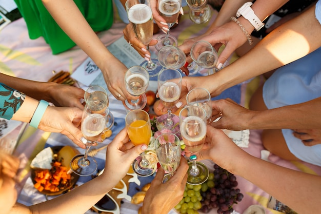 Group of people having outdoor picnic meal togetherness dining toasting glasses. summer weekends