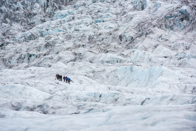 Group of people hike glacier