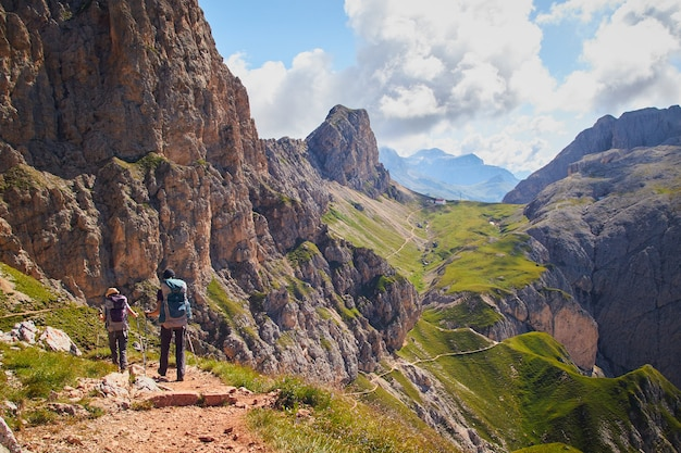 Group of people hiking in the mountains of schlern-rosengarten nature park in italy