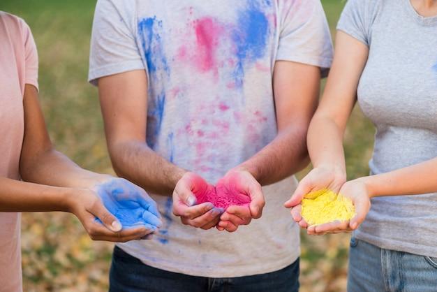 Gruppo di persone che tengono i colori in polvere